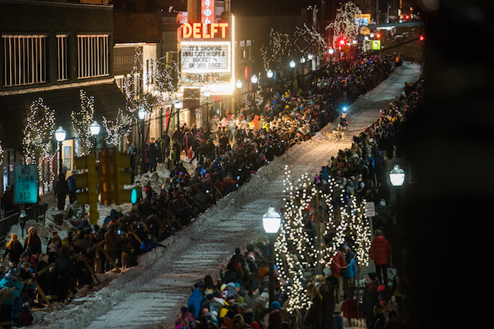 Crowds line the streets of Downtown Marquette as a dog sled team races by